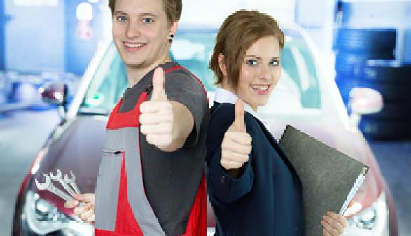 Mann in Arbeitshose und Frau im Anzug stehen vor einem Fahrzeug in einer Werkstatt und geben beide einen Daumen nach oben. © Karin & Uwe Annas, stock.adobe.com