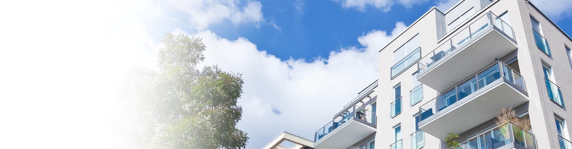 Ein moderner, fünfstöckiger Wohnbau unter blauem Himmel, vor einem Baum © Tiberius Gracchus, stock.adobe.com