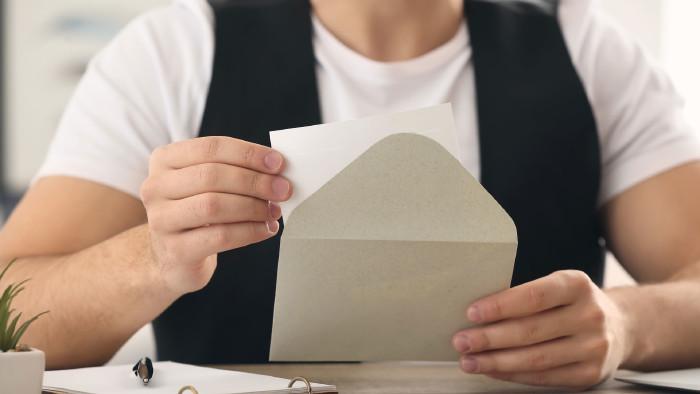 Ein junger Mann mit Weste zieht ein Schreiben aus einem geöffneten Kurvert. © Pixel-Shot, stock.adobe.com
