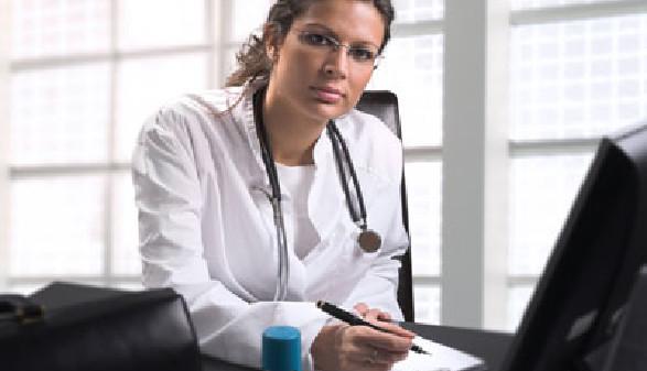 Ärztin sitzt beim Schreibtisch © Nyul, Fotolia