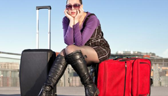 Frau sitzt auf einem Reisekoffer © Zoe, Fotolia
