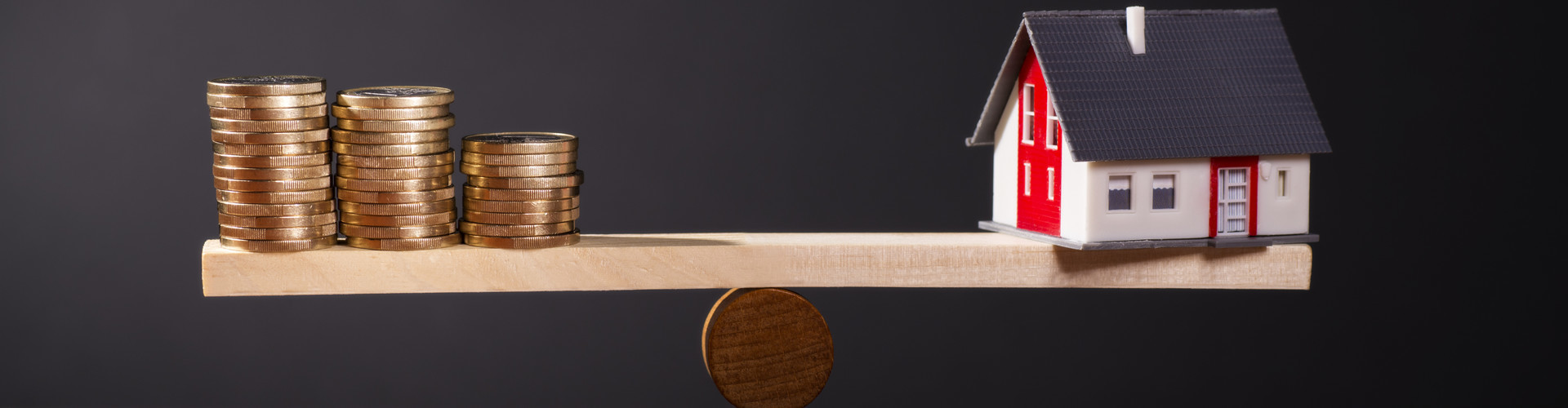 auf einer hölzernen Wippe stehen links drei Münzstapel und rechts das Modell eines Hauses, die sich die Waage halten. © Eisenhans, stock.adobe.com