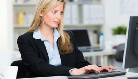 Eine Frau im Anzug sitzt am Schreibtisch und blickt auf den Computerbildschirm vor sich. Im Hintergrund sieht man ein Regal mit Ordnern. © Racle Fotodesign, stock.adobe.com