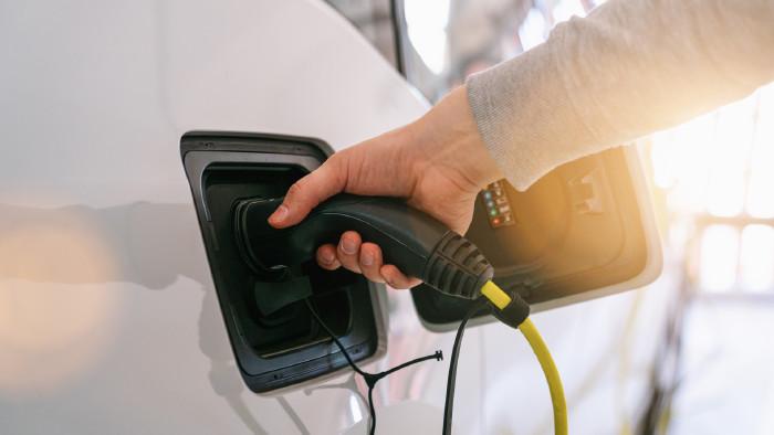 Ein Arm fürht einen Ladestecker in den Ladesanschluss eines elektrischen Fahrzeuges. © rcfotostock, stock.adobe.com