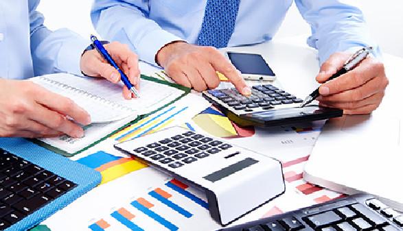 Zwei Büroangestellte führen Berechnungen mit Taschenrechner durch © Kurhan, Fotolia